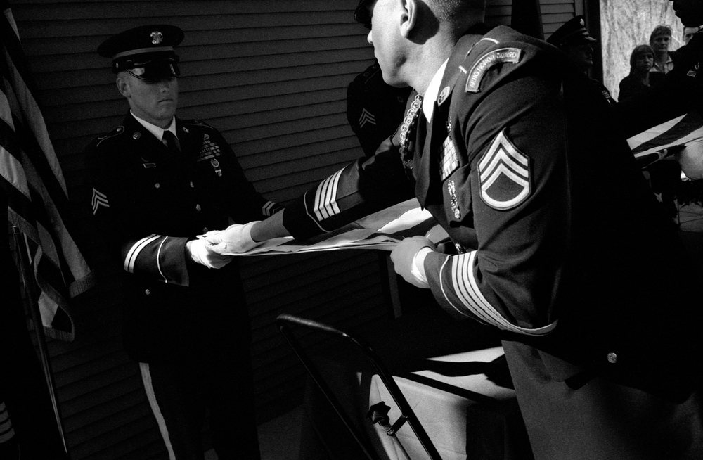 National Guard soldiers fold a flag at the funeral of SPC Dirk Terpstra who committed suicide shortly after returning home from Afghanistan; Ft. Custer National Cemetery, Augusta, Michigan, 2010. The night of his death, Terpstra visited a bar with friends where he became drunk and then shot himself in a neighbor's front yard.