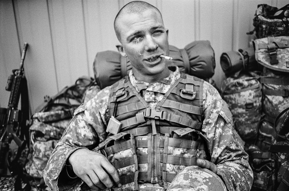 SPC Ryan Cooley smokes a cigarette while on a break during training drills at Fort Drum, New York, 2010.