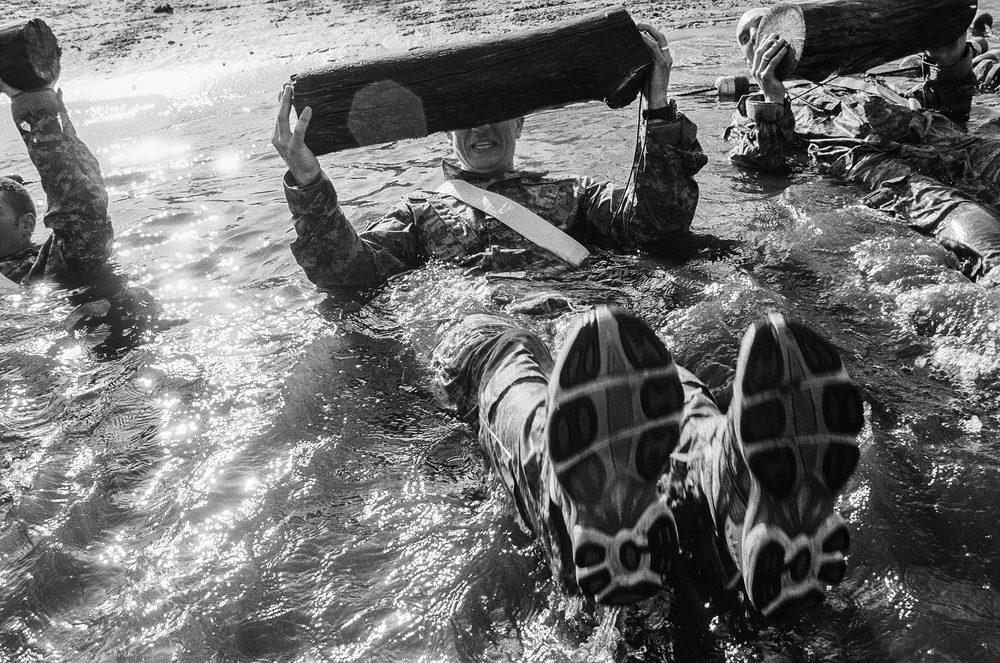 LT John Cote swims with a log during a training drill at Fort Drum, New York, 2010.