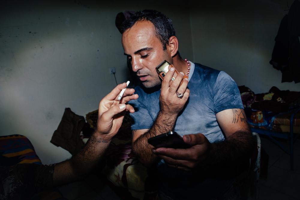 An NPU militia soldier shaves, looks at his phone and smokes a cigarette at an NPU military base near Sharafiyah, Northern Iraqi Kurdistan.