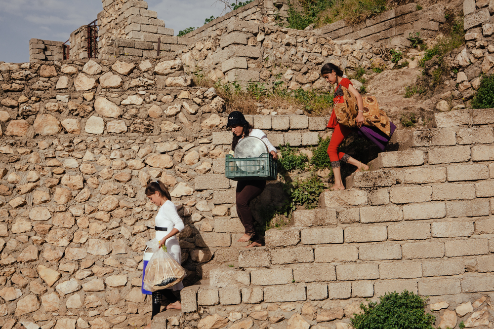 Girls carry food and other items down a staircase at Lalish, the most sacred and only Yezidi temple in the world,in Northern Iraqi Kurdistan.