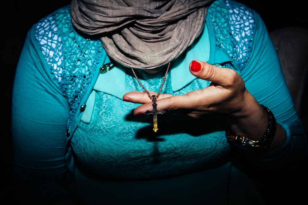 An Assyrian Christian woman shows her cross necklace at a Christian revival in Dohuk, Northern Iraqi Kurdistan.