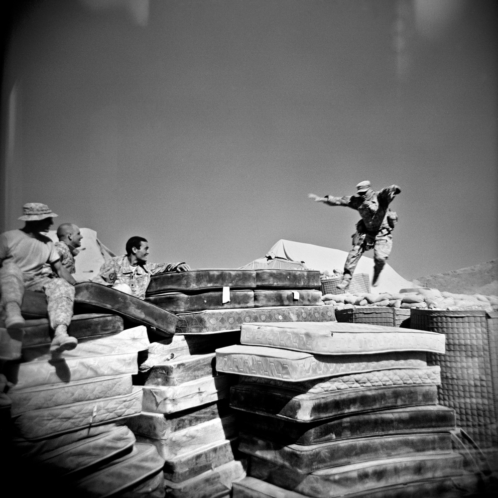SGT John Virgadamo, SPC Matthew Ledford, and SPC Brian Lucey watch  SPC Adam Ramsey, right, jump onto a pile of mattresses at COP Charkh in Logar Province.