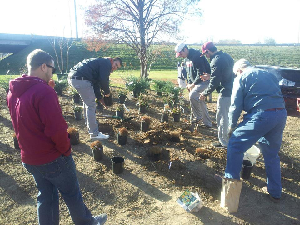 Volunteers get their hands dirty to help beautify the entrance of I-64 West and Spring Street.