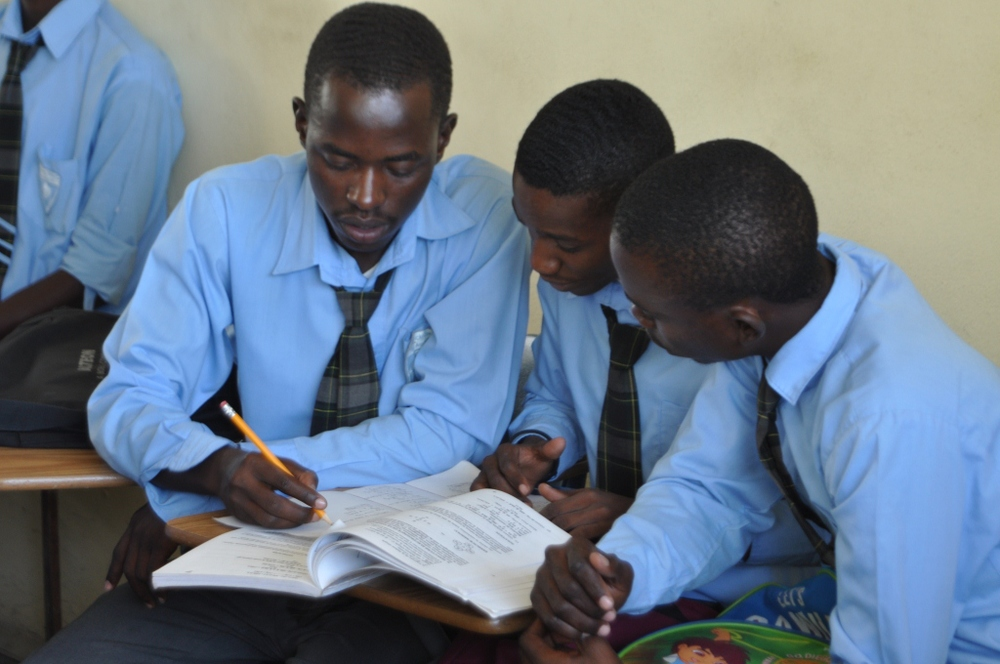 Senior boys share an exam study book