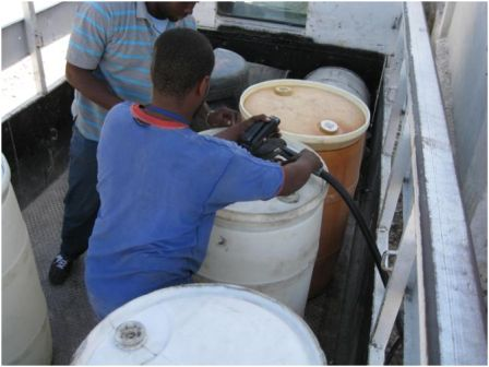 Filling eight, 60 gallon drums with diesel fuel from the World Food Program.