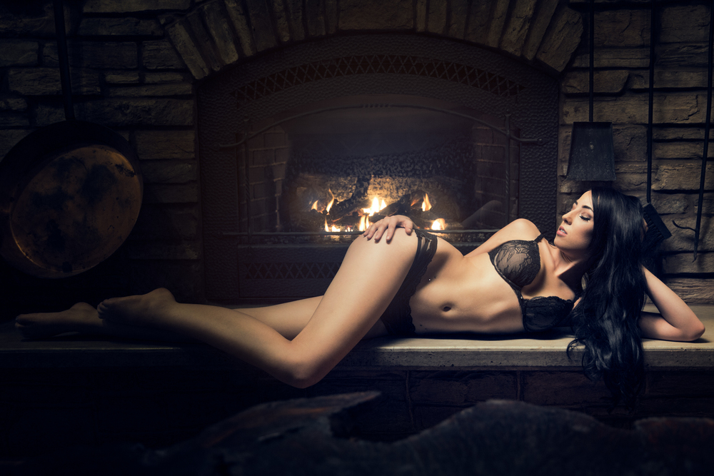 tasteful boudoir photography of Vanessa near a fireplace.