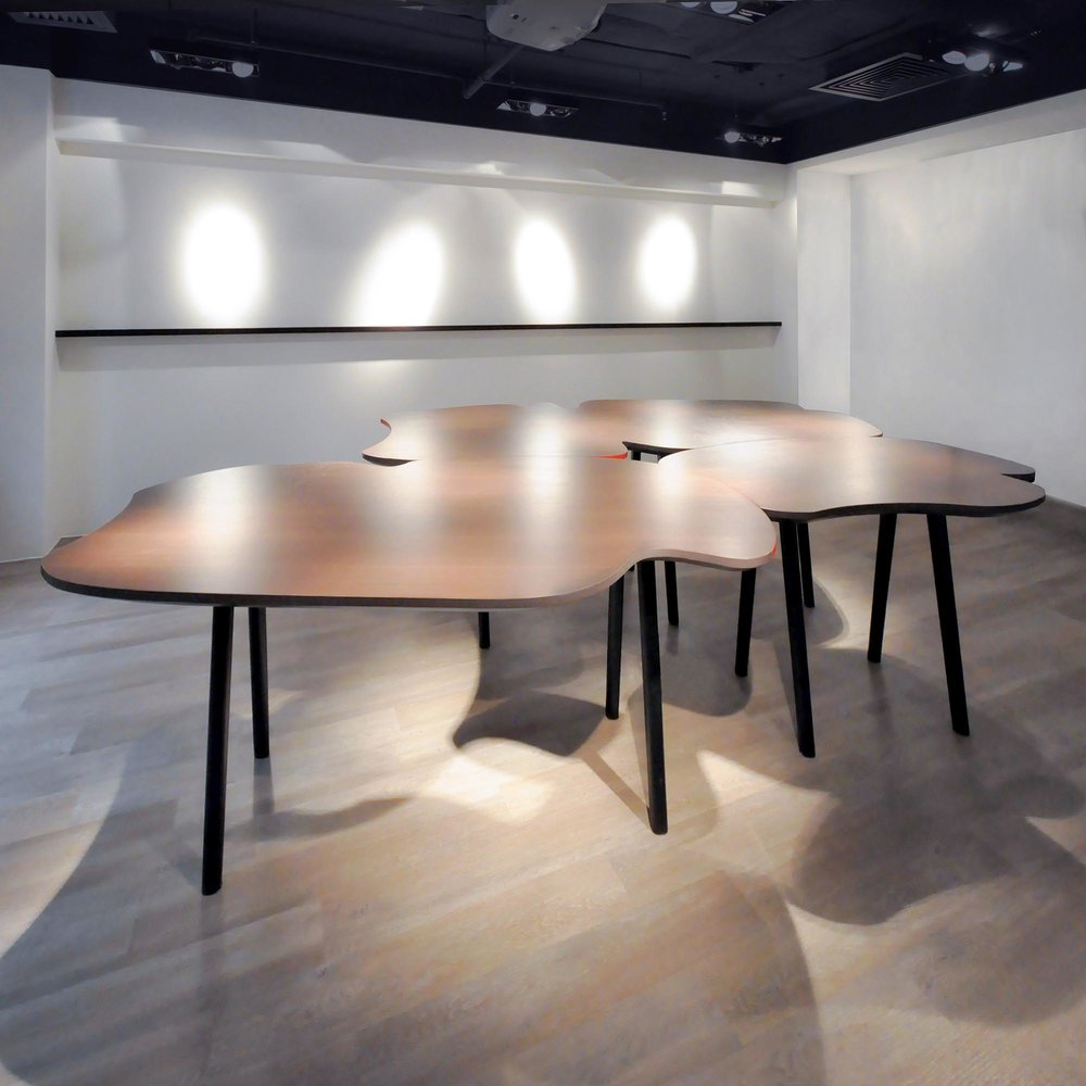 A set of wiggly and curvy conference tables was designed to break down the atmosphere of a traditional corporate conference room. These tables can be playfully re-arranged into four configurations to adapt to different scenarios - from one long table for large-scale meeting, to smaller clusters for small-scale meetings — a reminder of the state of flux as the key to creativity.
