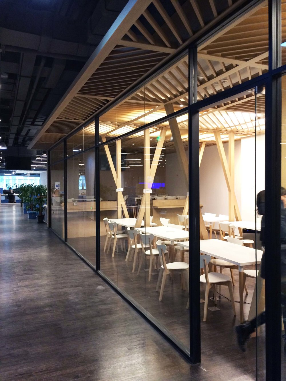 The pantry was designed to feel calm, airy and fresh. A timber slatted canopy with artificial skylights defines the space, while tree-like columns accentuate its verticality. A full height glass wall replaced a solid partition to allow natural daylight to enter the space from the building's atrium.