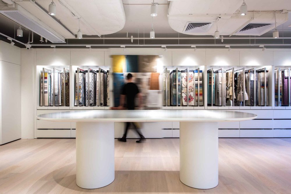 The main backdrop of the open space is a high density display and storage wall, with hanging fabric products, and drawers for samples and catalogues. Two sets of full height sliding panels encourages customers to push and pull to discover the products behind, and allowing their selections to be viewed vertically on the hanging rails of the sliding panels. A large 3 metres long island table is designed for customers to lay out their fabric selections horizontally to carry out inspection and discussions.