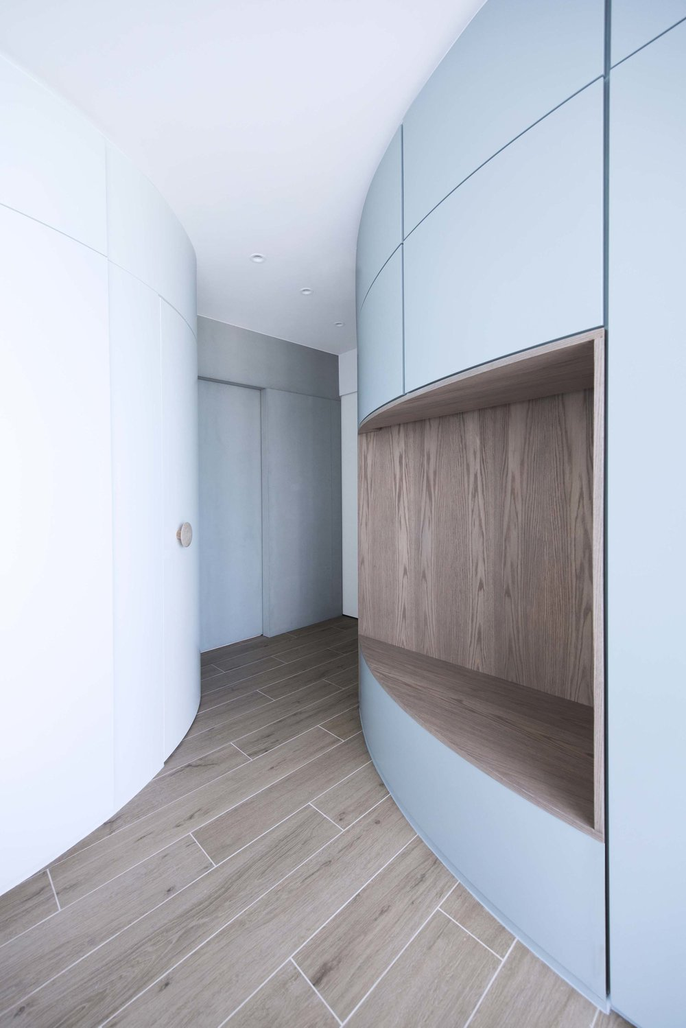 An innovative solution is created to address the relationship between the parents spaces which are the master bedroom suite and the study room, the children spaces, and the common social spaces. In order to create privacy for the parents, a concealed pocket sliding door can be pulled out from the concrete volume to divide the master bedroom suite and study room away from the rest of the apartment. The sliding door has acoustic separation to ensure the noise from the children play spaces will not penetrate to the study room where the parent has to carry out focused works. To further increase privacy for the study room, an additional sliding door is designed to partition the study room from the master bedroom suite, this will allow flexibility for one parent to be sleeping in the master bedroom while another might be working in the study. When both sliding doors are opened, the two elements of the flowing blue volume and the concrete volume would appear to flow continuously throughout the entire apartment, fluidly connecting the parents spaces back to the open spaces of the apartment.
