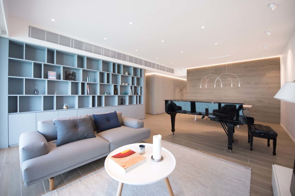 The first element is a curvy blue volume that forms half of the apartment; it begins its stream as a bookshelf with random niches from the lounge into a corridor that conceals the children room and guest room, and flows towards the master bedroom and forms a storage volume with a seating niche.  The overall floor finish is a ceramic tile with wooden texture is used for the flooring which is durable as a hard surface but provides visual warmth to the space. The tiles also form the wall finish for the dinning area, creating a comfortable setting with a pendant light and an extendable table for six to ten people.
