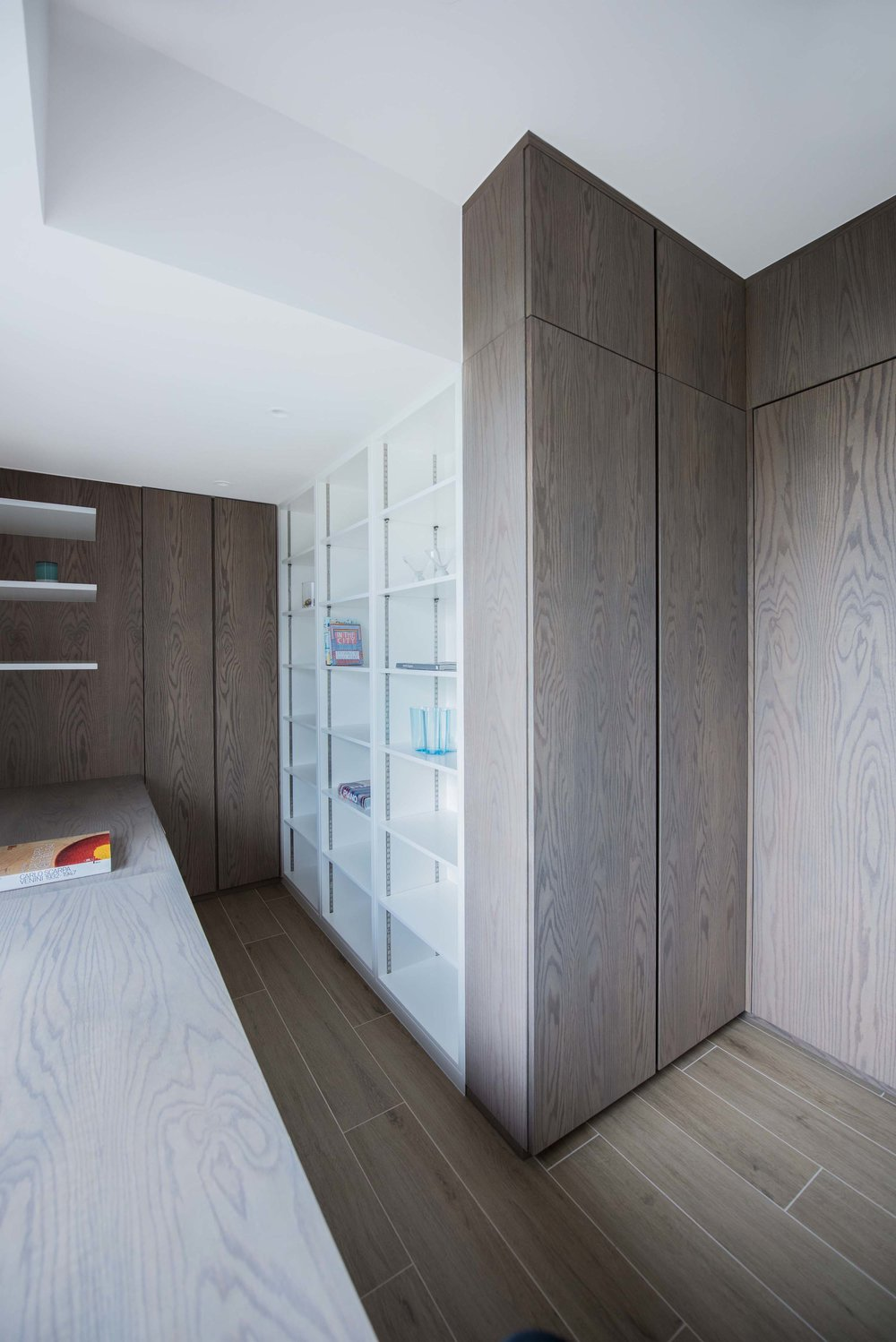 The study room has high density storage for books and filing, as well as a bespoke built in desk with cable management for computer and printers. A magnetic writable surface is integrated into the white walls of the room.