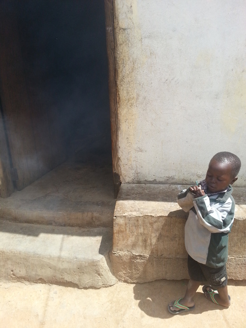 This little boy, Fineas, hung around me the whole time I was cooking. Now we were waiting patiently for the rice to cook over the fire.