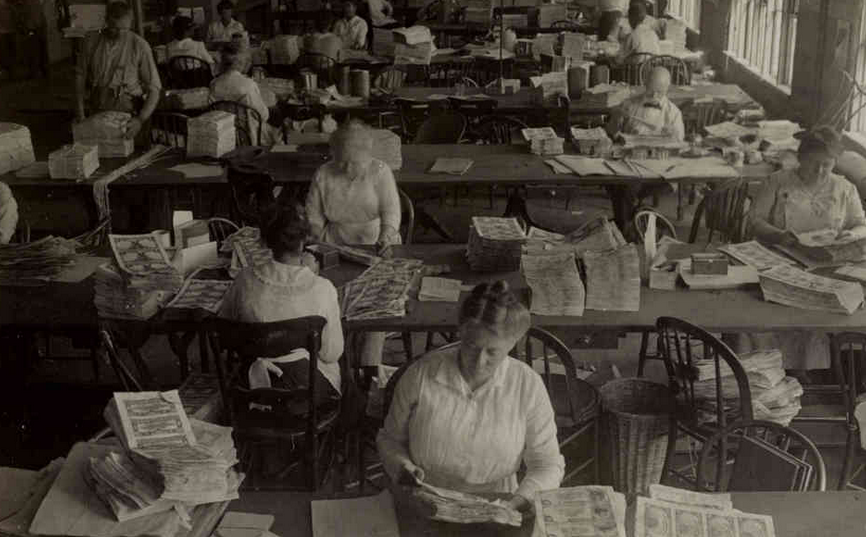 Workers inspecting sheets of money for printing flaws and smudges, circa 1917.