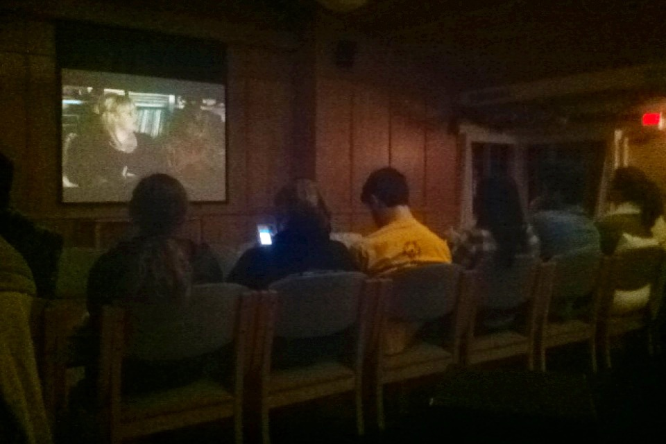 A group of students kicking back and watching Pitch Perfect together.