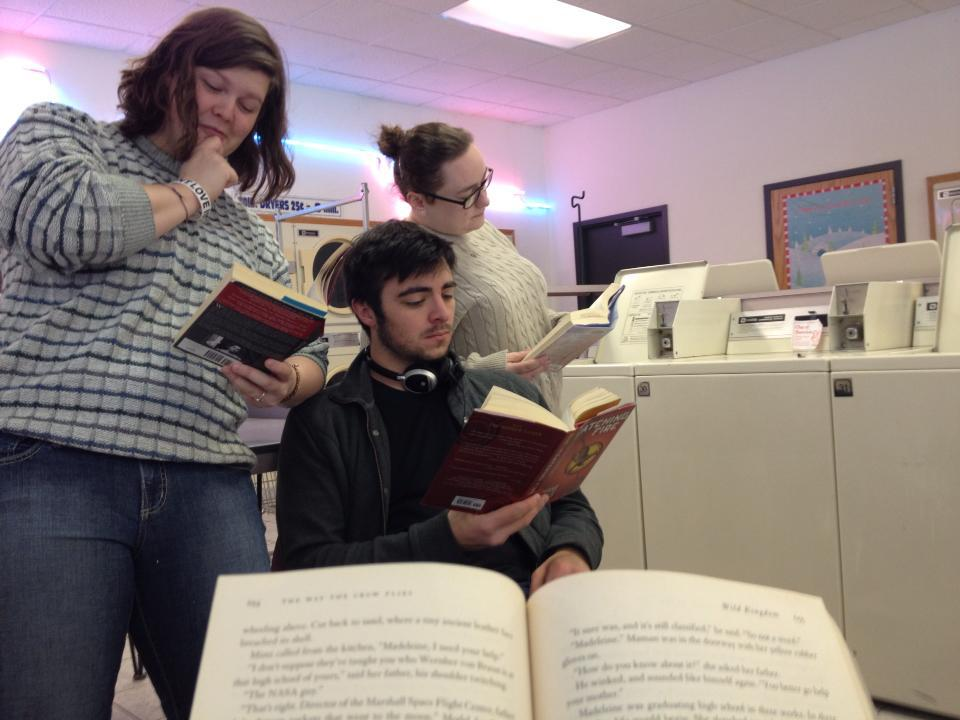 Abi, Jessica, Luke, and Portia wait for their laundry to finish by having a book party right in the laundromat.