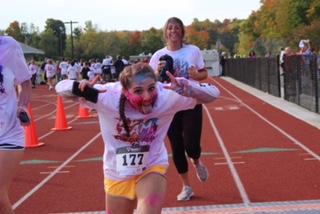 Juniors Mia Potamianos and Jenna Vespi cross the finish line of the Red Ram Color Run