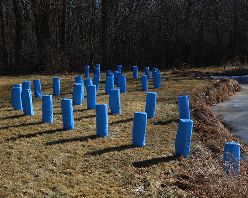 """Posts in a Blue Wave, 2018, installation; tarp 24"""" x 8"""" x 8"""" (36 pieces), weights, distributed newsprint 3"""" x 4 1/2"""""""
