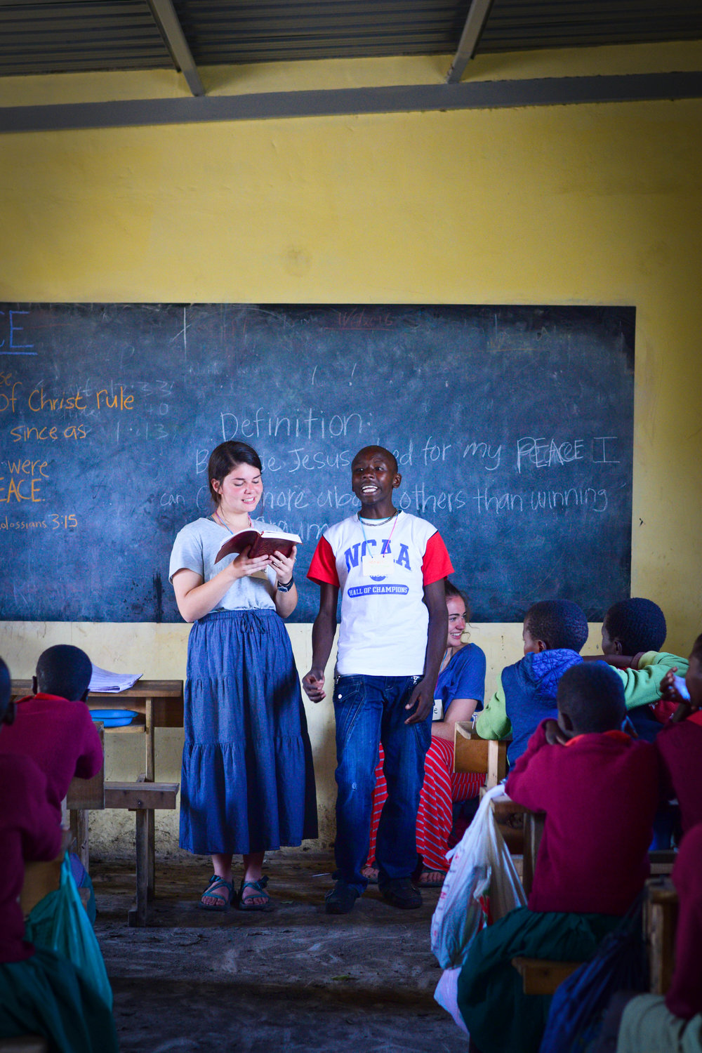 Maddie (left) stands before a classroom of students in East Africa alongside a Rejoice Project peer leader from one of 6 community children's camps taught on the virtue of Peace in 2016.