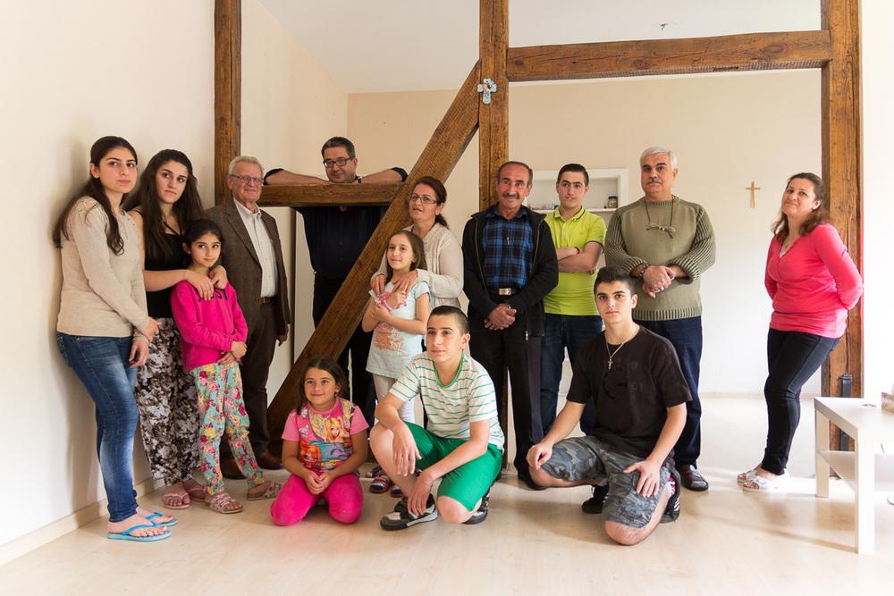 Die beiden syrischen Familien gemeinsam mit Verwaltungsrat Peter Lesko (4.v.l.) und Pfarrer Stephan Gras (ganz hinten) in der Wohnung am Kirchort St. Elisabeth. Foto: Benjamin Dahlhoff