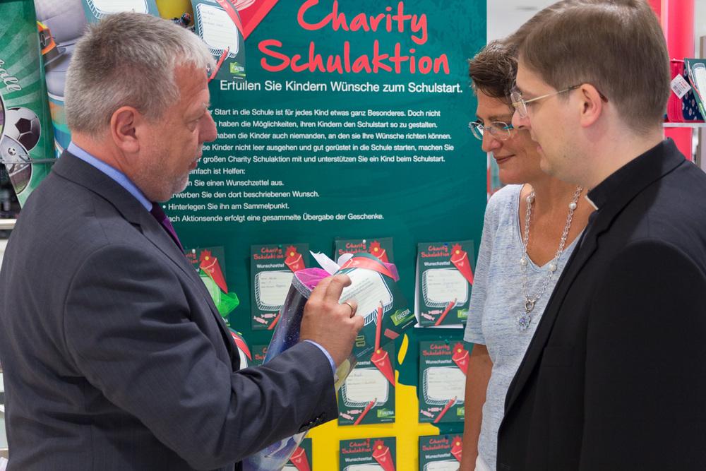 Filialgeschäftsführer Karsten Sinnig stellt Dr. Julia Fauth und Pfarrer Klaus Nebel die Schultüten im Erdgeschoss der Galeria Kaufhof vor.