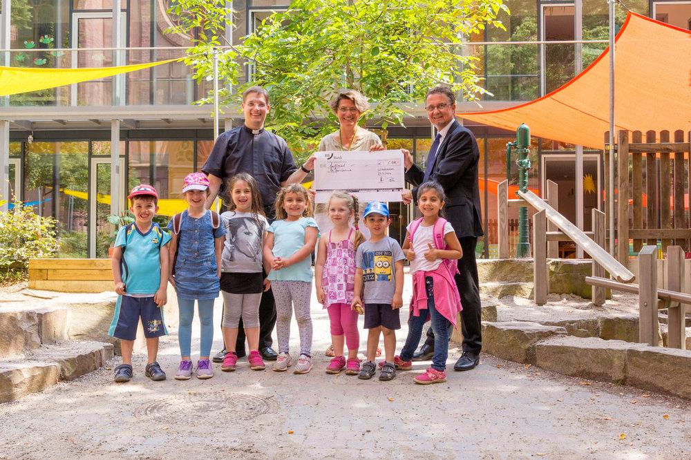 Für die BBBank übergibt Herr Erben (r) einen symbolischen Scheck über 5000 Euro an Dr. Julia Fauth (m) und Pfarrer Klaus Nebel (l).