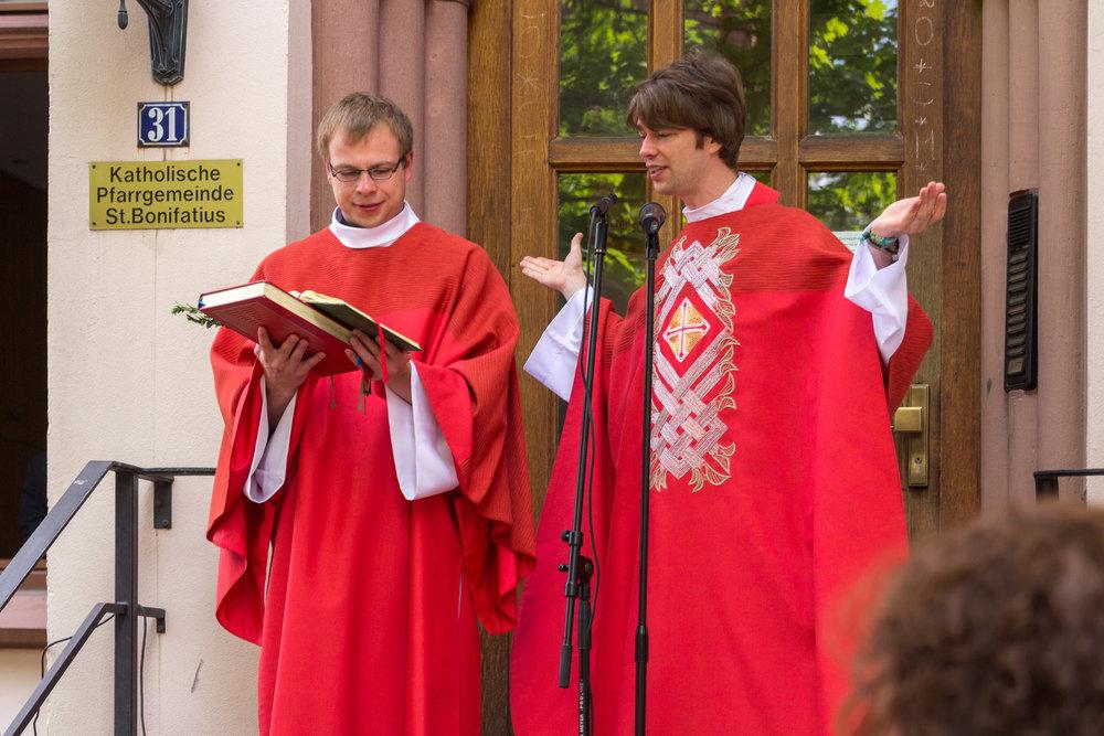 Die Kapläne Radoslaw Lydkowski (links) und Simon Schade (rechts) bei der Palmweihe auf den Stufen des Pfarrhauses St. Bonifatius. (C)2014 Benjamin Dahlhoff