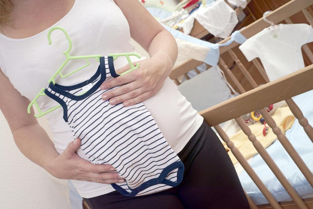 Kopie von schwangere Frau mit Babystrampler