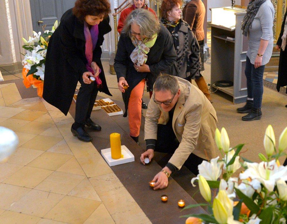 Als Symbol für den Frieden zündeten die Besucherinnen und Besucher in ökumenischer Verbundenheit auf den Treppen vor dem Altar in der Marktkirche eine Kerze an. Foto: Andrea Wagenknecht/Ev. Dekanat Wiesbaden