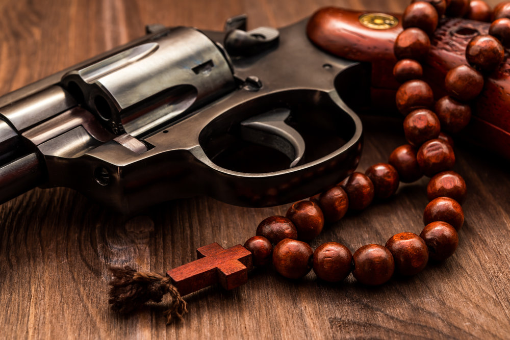 Revolver and a rosary on the wooden table