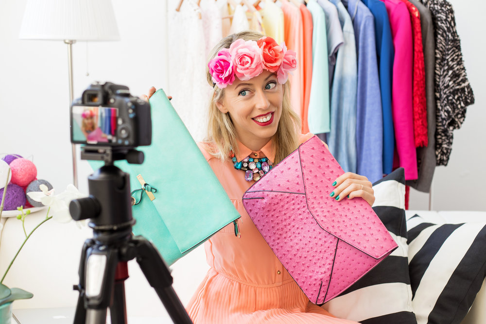 Fashion blogger taking a picture of two clutch bags