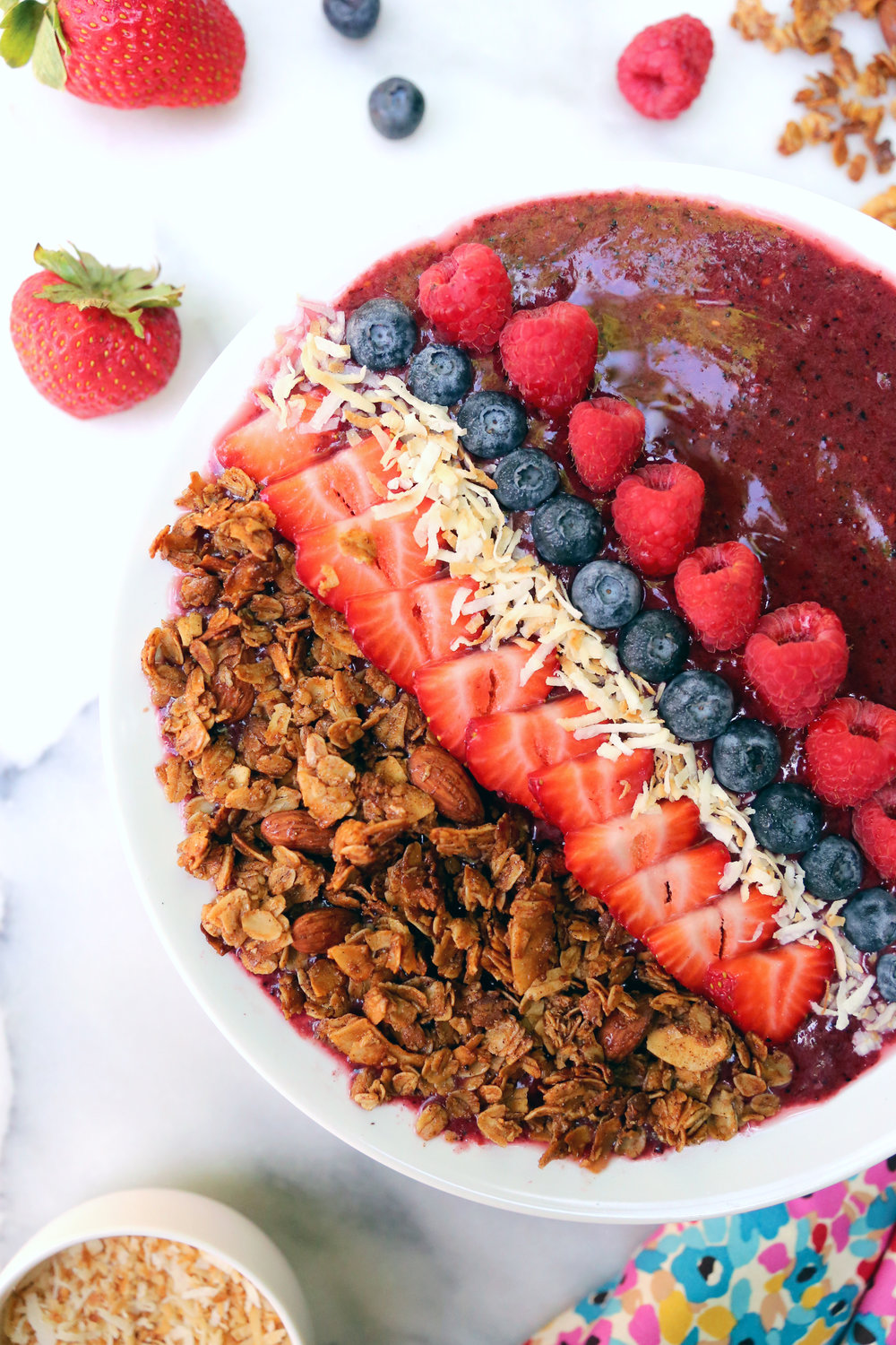 A berry smoothie bowl topped with fresh fruit, toasted coconut, and granola. Unusuallylovely.com