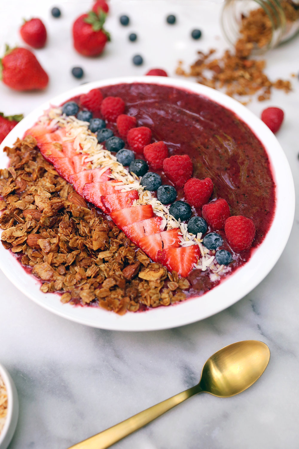 Berry Smoothie Bowl topped with granola, toasted coconut, and fresh berries. Get the recipe from the Unusually Lovely Blog.