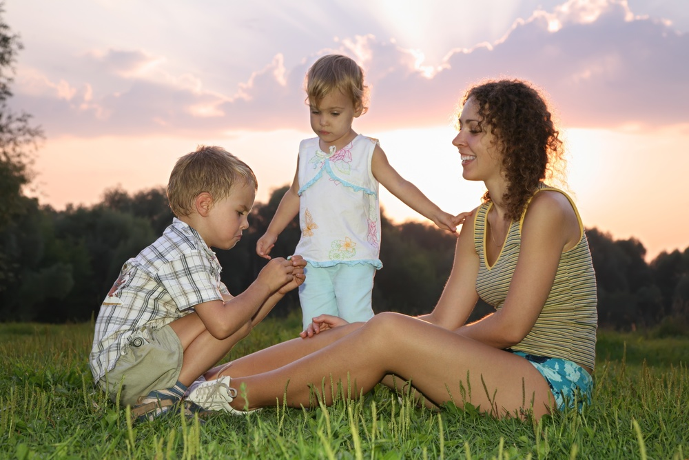 mother with children sits on the grass