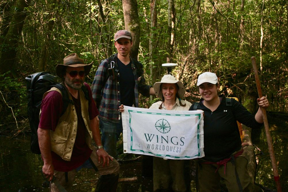 Becca Peixotto (holding flag) and her team on a hot and humid day in the Great Dismal Swamp. Photo courtesy of Becca Peixotto.