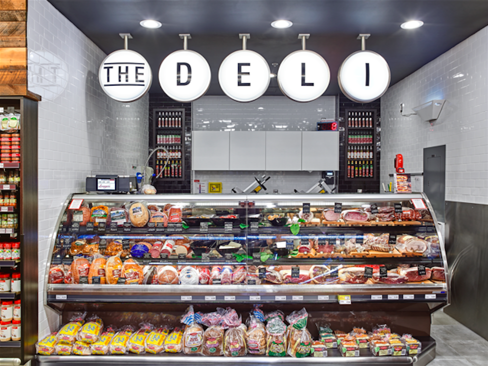 "Deli - Inspired by old delicatessen signage, the internally illuminated ""Deli"" signage calls out the full service deli counter at the back of the store."