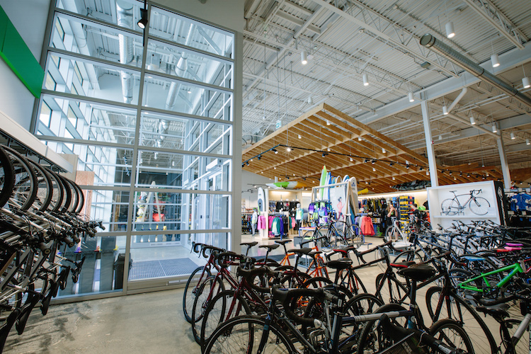 Windows at the store's entrance feature bright natural light, welcoming shoppers into the store. Cycling merchandise is on display in the front of the store, with LVL wood beem canopy in the distance.