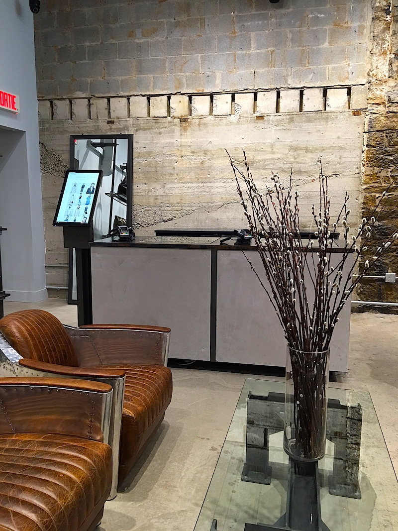 Cash desk, exposed concrete walls, leather/metal furniture. Product not available in the store can be ordered on the screen in the photo, to be shipped the next day. Photo: Maxime Frechette.