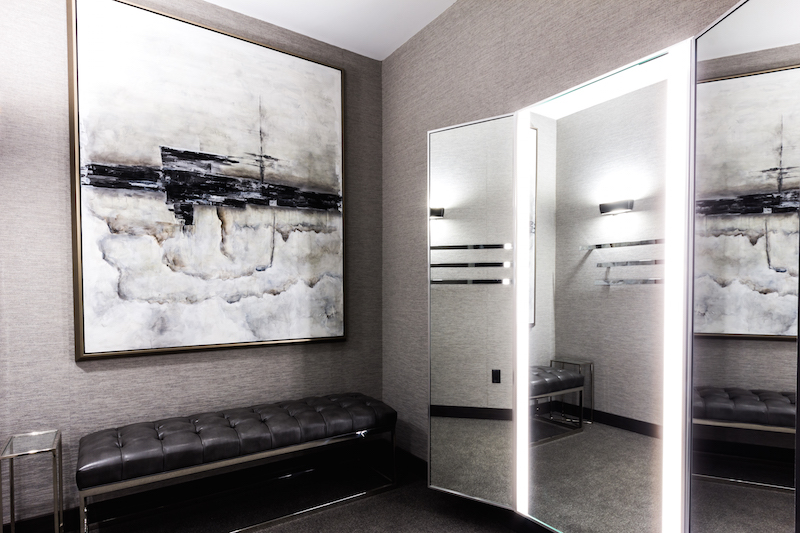 Large dressing room, featuring luxurious wall coverings, leather seating and artwork.