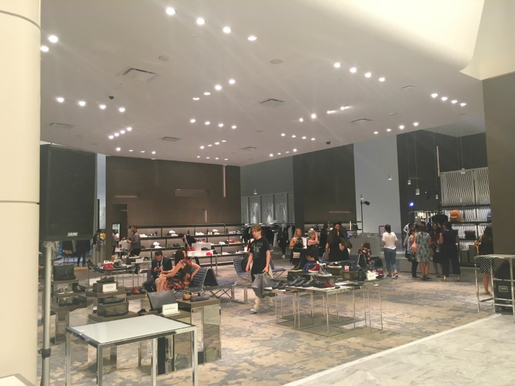 Large men's footwear department in the foreground, with men's departments in behind. The space is flooded with sunlight during the day, and this photo was taken in the evening. Photo: Chantal Mizerski, Retail Council of Canada.