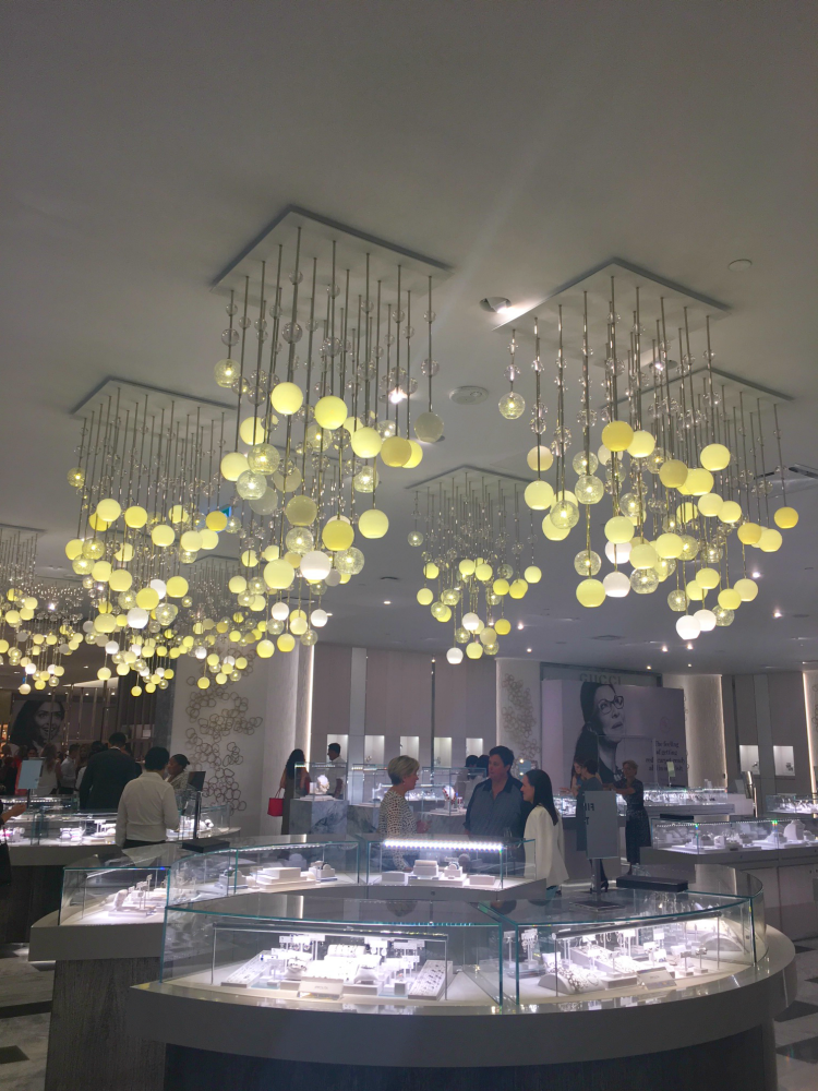 Dramatic lighting hangs from the ceiling in the store's jewellery department. A Gucci boutique can be seen behind hoarding in the back. Photo: Chantal Mizerski, Retail Council of Canada.