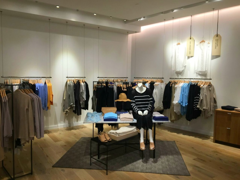 Simple, elegant hanging racks against white walls at Sherway's Eileen Fisher store. Photo: Pace Construction