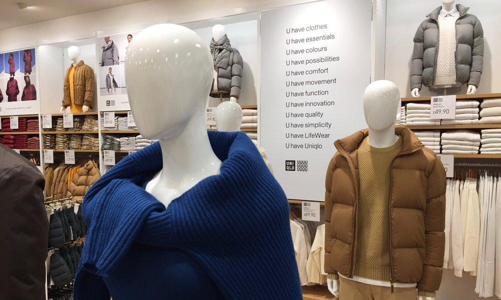 A ladies blue sweater and mens beige jacket are both part of Uniqlo U