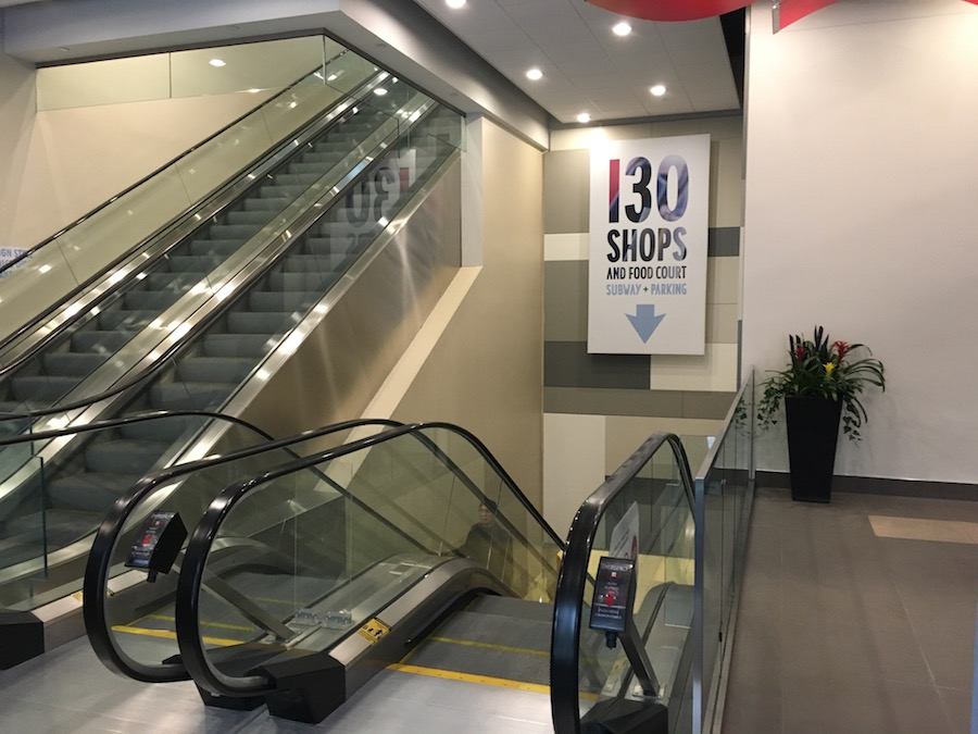(Ground level entrance to the Shops at Aura, accessed from an escalator.)