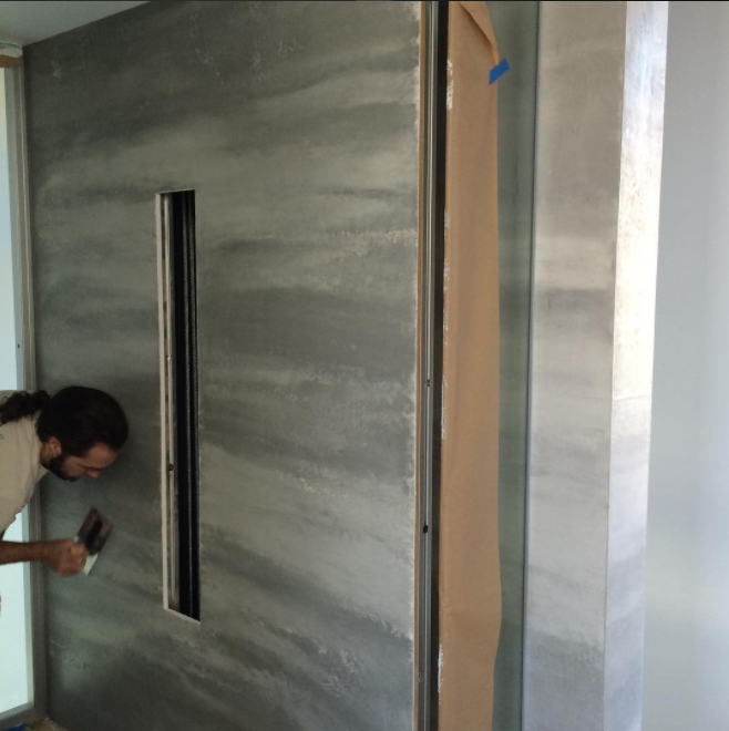 (Applying a tricolor Venetian plaster finish to a glass elevator. Photo: Darrell Morrison