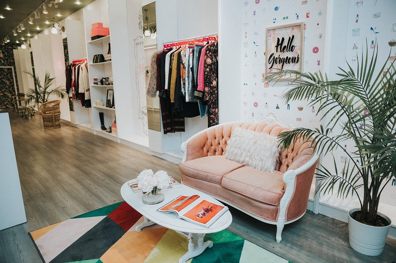 (Seating area with curated 'melissa must haves' fashions on the wall.   Photo: Bayview Village) )
