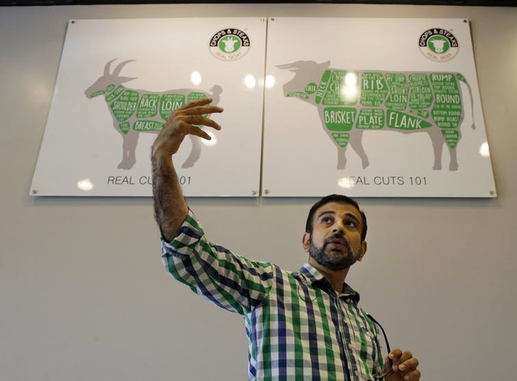 Gul Muhammad at his Chops and Steaks butcher shop in North Brunswick, N.J., discusses halal meat orders for customers in 2015. Shops like his must be vigilant ensure the meat is verified halal — a task blockchain technology could aid.  (AP Photo/Mel Evans)