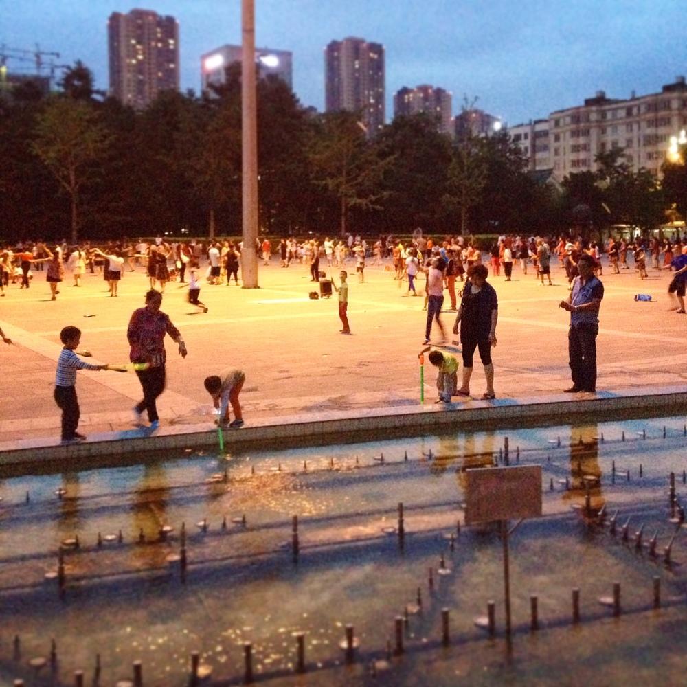 Normalt torgliv en vardagskväll. Vattenlek, badminton och otaliga motionsdansgrupper med egna ljudsystem.