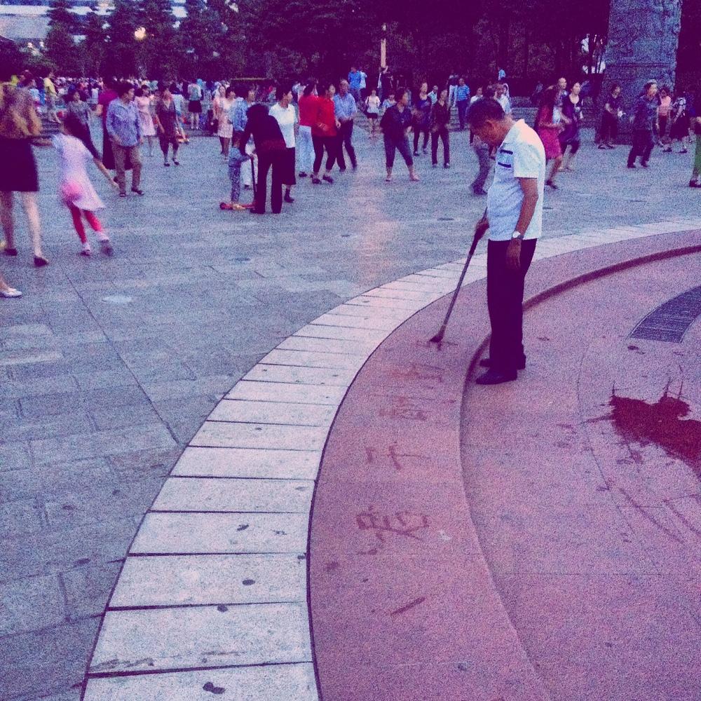 En man som övar kalligrafi med vatten från fontänen.